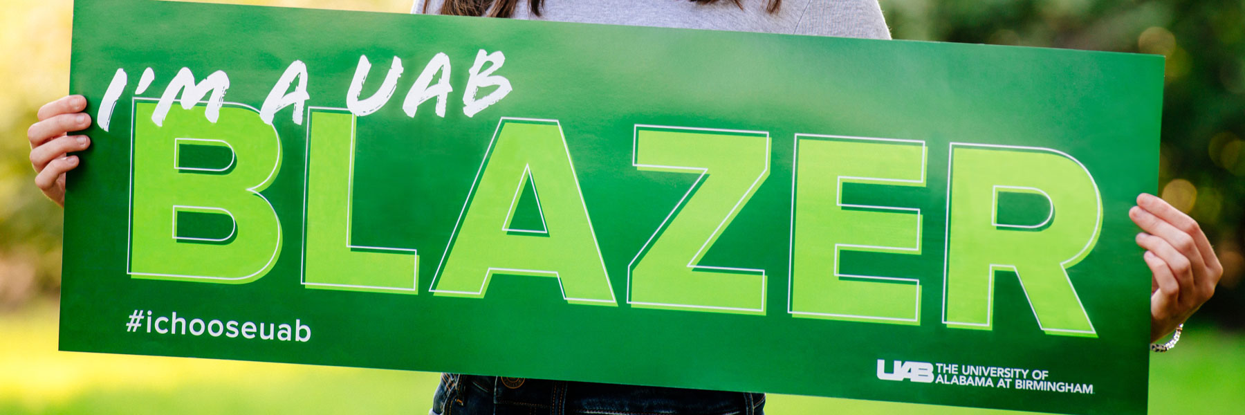 Student holding I'm a UAB Blazer sign