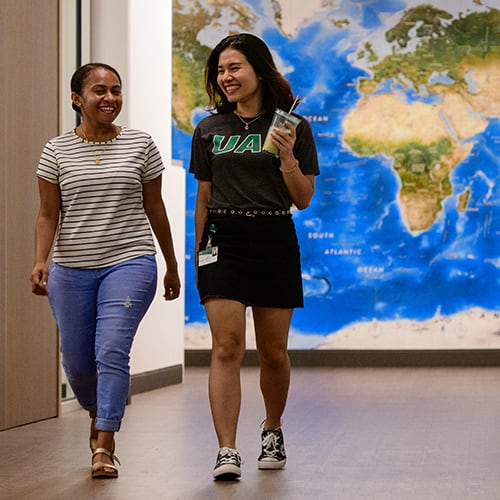 Two students walking down the hall with a map of the world behind them.