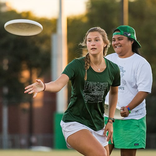Two students playing frisbee.