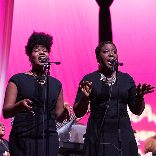 Two women singing onstage.