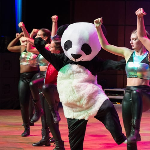 Femail students performing with person dressed in a panda suit.