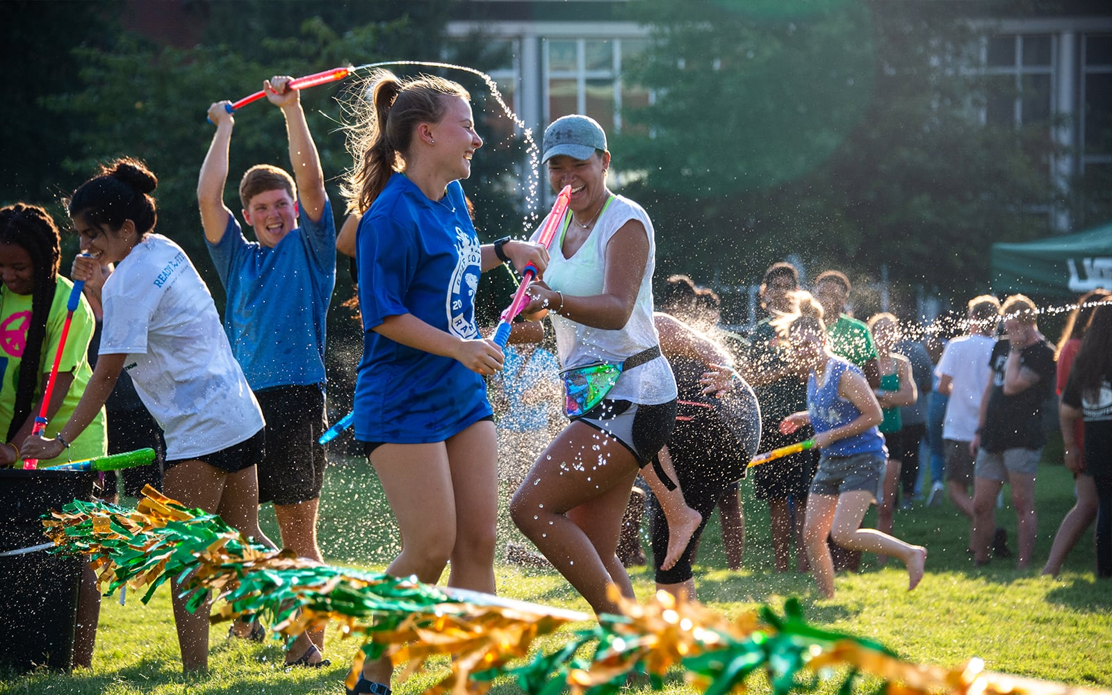 Students having water fight on campus green.