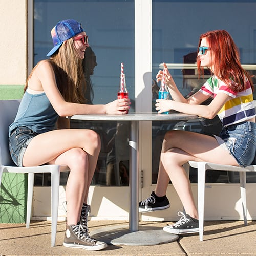 Two students sitting at a table drinking sodas.
