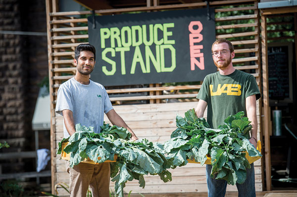 Students holding plants while standing in front of produce stand.