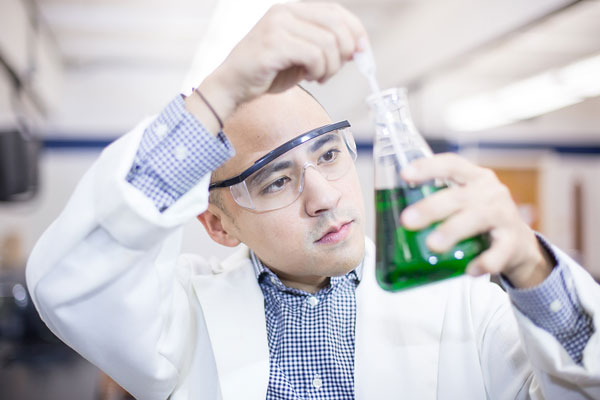 Man in lab coat using beaker.