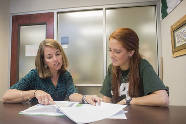 Advisor with undergraduate student in an advising session reviewing documents.
