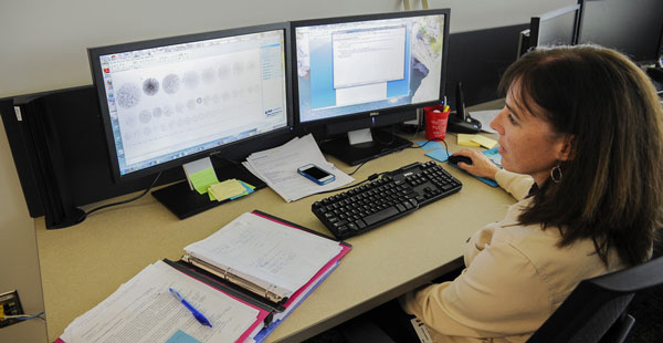 Woman working at a dual-monitor station.