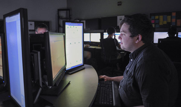 CIS student in a darkend computer lab.