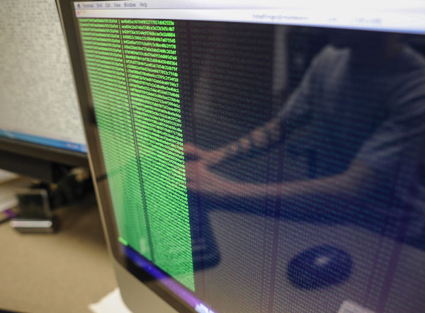 The reflection of a student can be seen on a computer screen full of code.