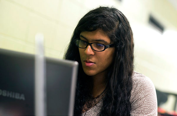 Female student in glasses at a laptop.