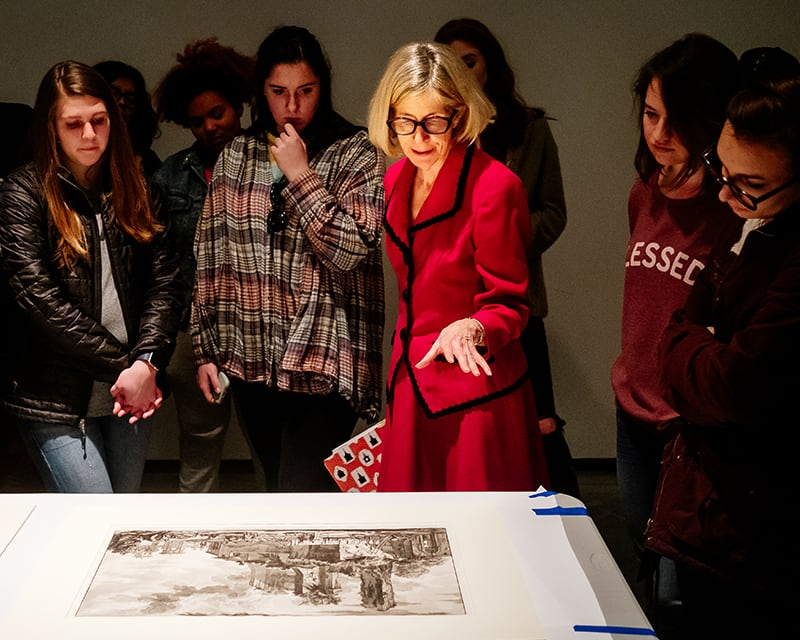 students and professor discuss art piece