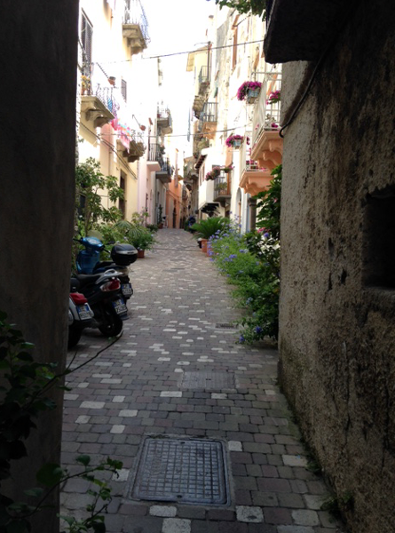 A narrow alley between two Italian buildings, with flowers, greenery, and motor scooters.