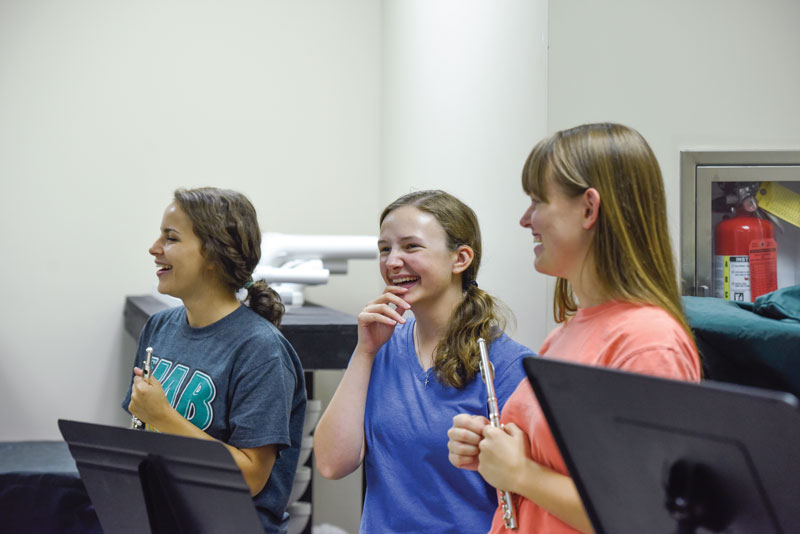 A trio of female flute players at band camp.