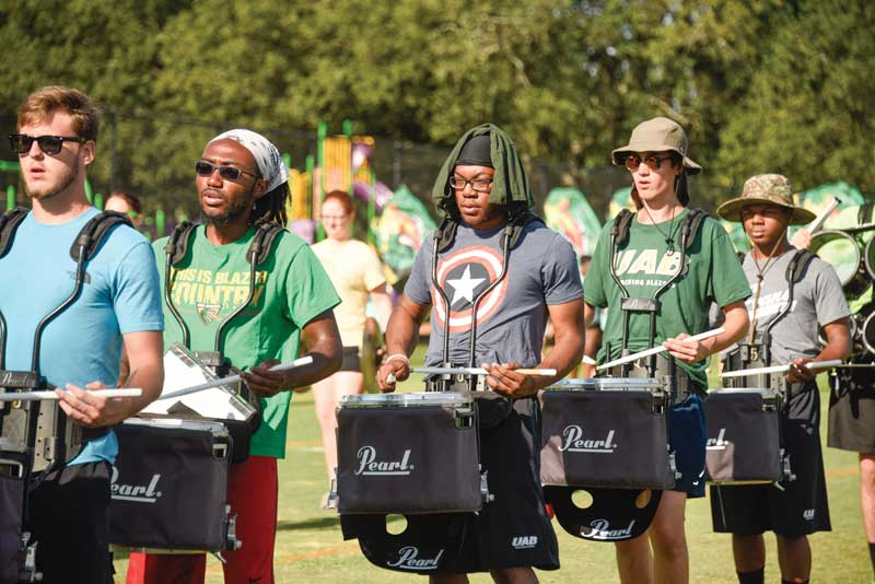 Drummers practicing on the field at band camp.