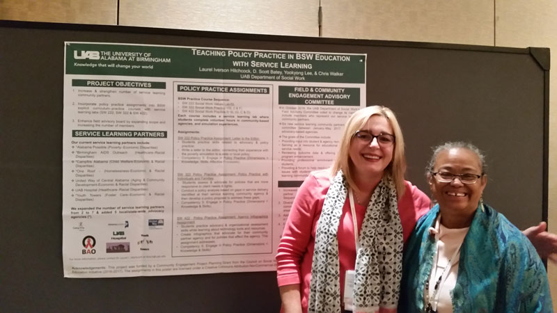 Laurel Hitchcock with other UAB faculty member in front of poster presentation.
