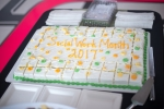 "A white iced cake reading ""Social Work Month 2017"", with yellow and green icing decoration."