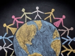 Chalk drawing of people holding hands around the Earth.