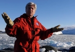 James McClintock in Antarctica, with much ice in the water behind him.