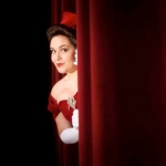 "Actress from ""A Ligttle Night Music"" peaking out playfully around a stage curtain."