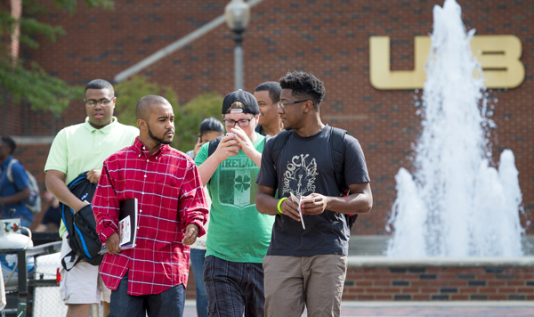 Students walking near a campus fountain.