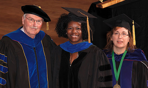 African American female student recieving her PhD hood at graduation ceremony.