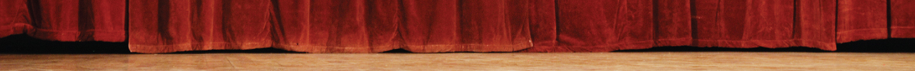 The bottom part of a red theatre curtain touching the stage.