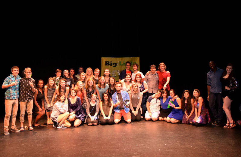 Group of around 30 Blazer Theatre Organization students on stage posing for picture.