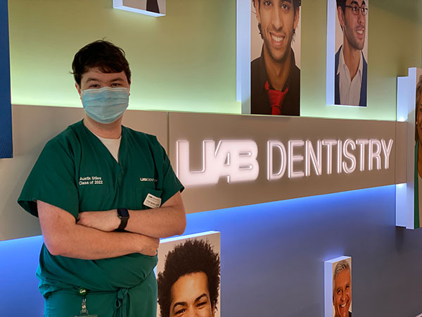 Austin Stiles wearing surgical mask and standing in front of UAB Dentistry sign.
