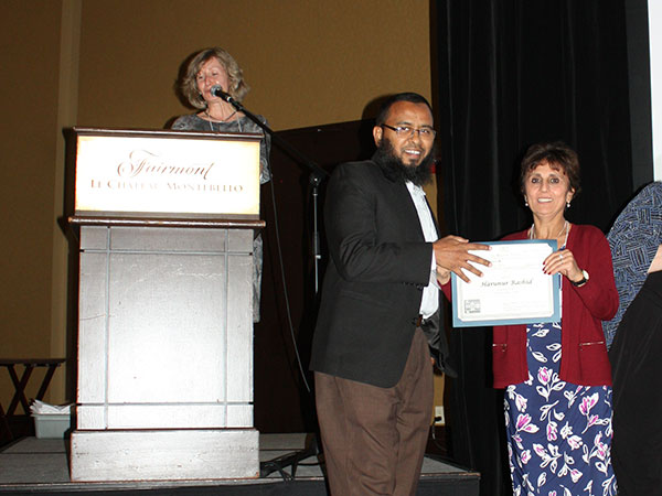 Harunur Rashid being presented with a certificate.