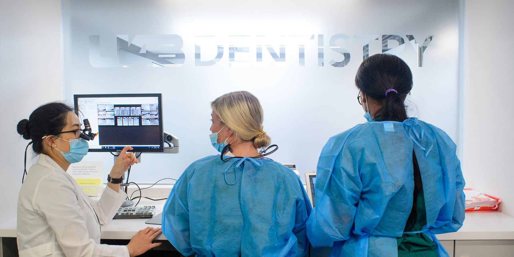 Three people wearing surgical masks and scrubs looking at x-rays in front of a UAB Dentistry sign.