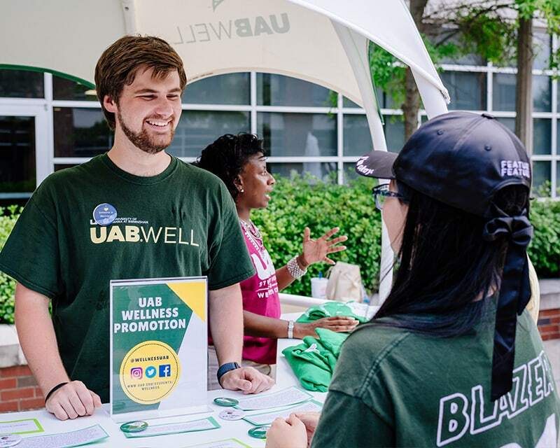 two people at a UAB wellness promotion booth