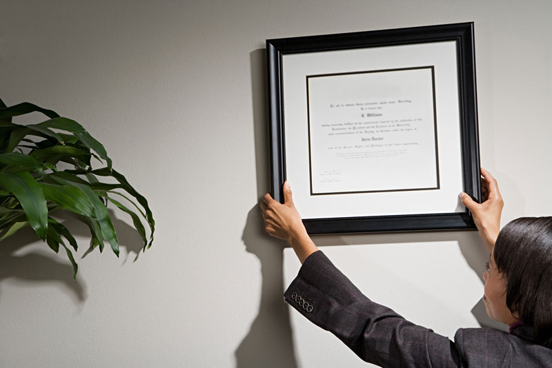 A woman hanging a framed diploma on the wall of an office.