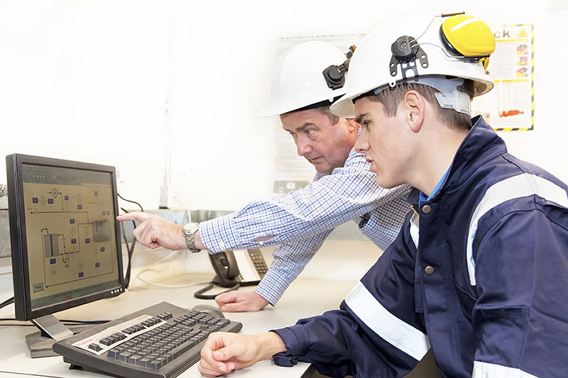 A senior and junior engineer discussing work in an on-site office.