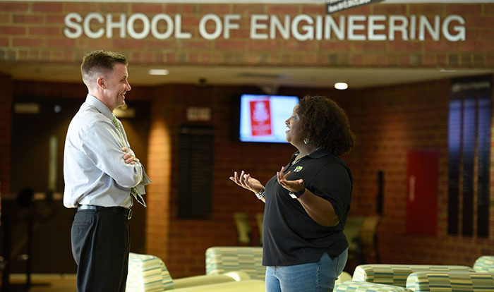 An Information Engineering Management graduate student speaking with a faculty member.