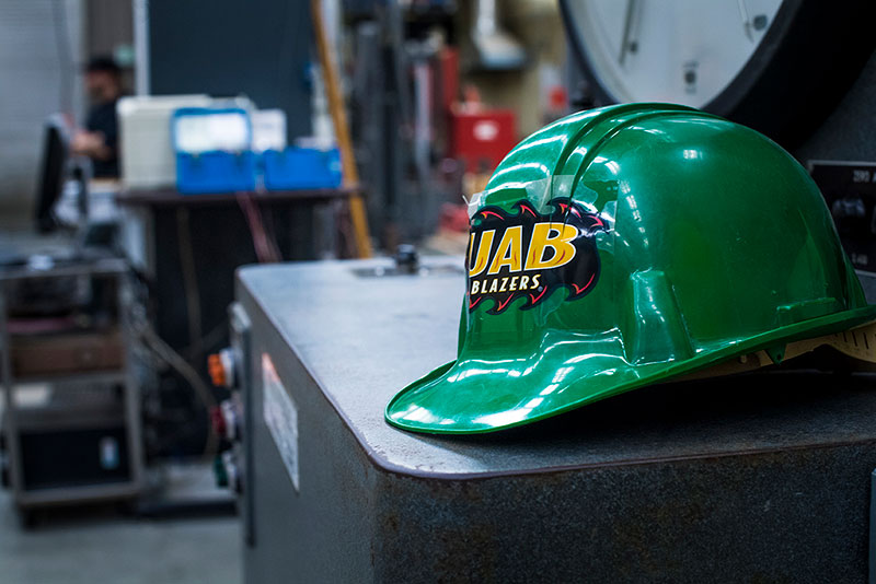A green hard hat with a UAB Blazers sticker.