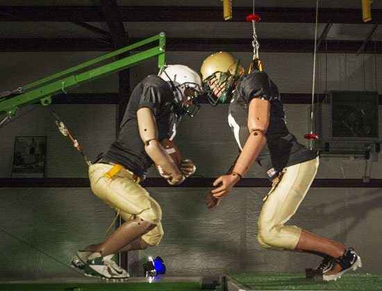 Crash-test dummies, one-of-a-kind sleds, and other hardware are used to evaluate football helmets.