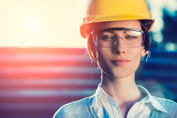 Woman with glasses wearing hardhat.