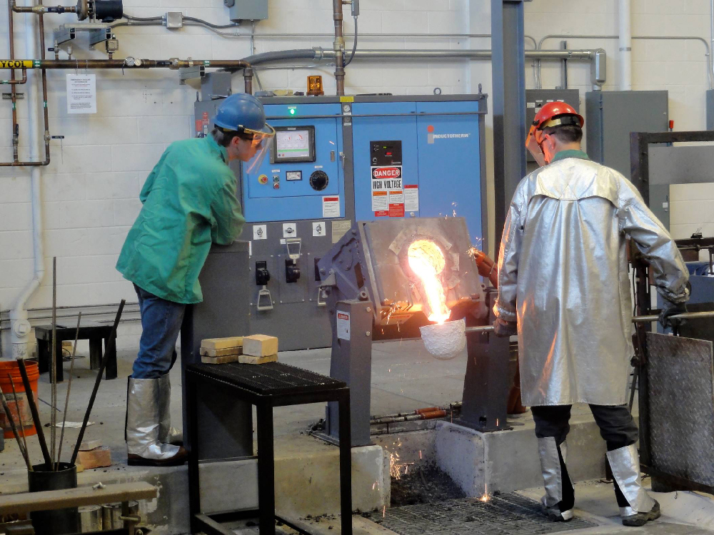Students in protective gear working with a molten material.