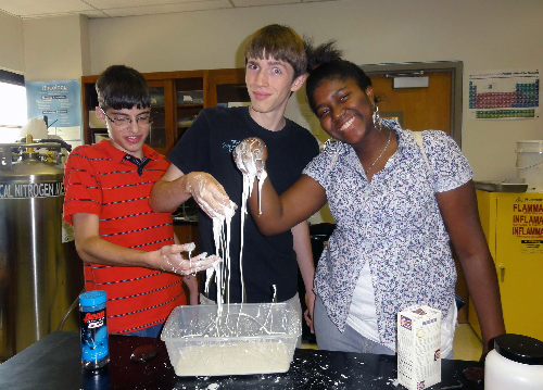 Students with hands covered in white goopy material.