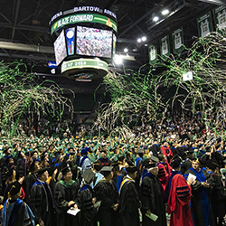 graduates celebrate under confettii in Bartow Arena.