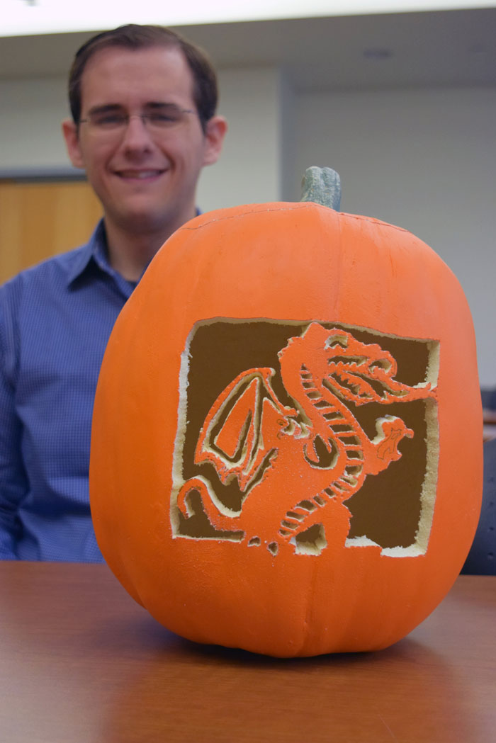 Michael Schultz with pumpkin carved in shape of Blazer the dragon.