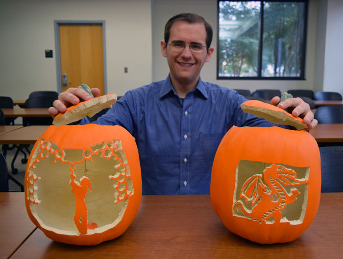 Michael Schultz with two carved pumpkins.