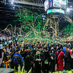 Students and faculty standing during commencement underneath green and gold streamers.