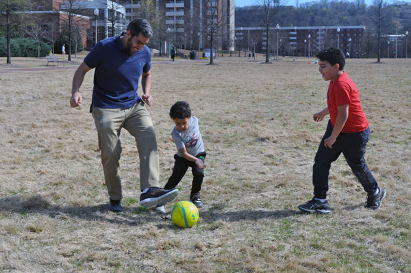 Hisham Abdelmotilib playing soccer with his kids.