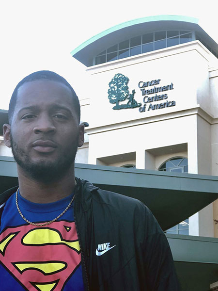 Rashad Hayes wearing a Superman shirt and standing outside of a cancer treatment center.