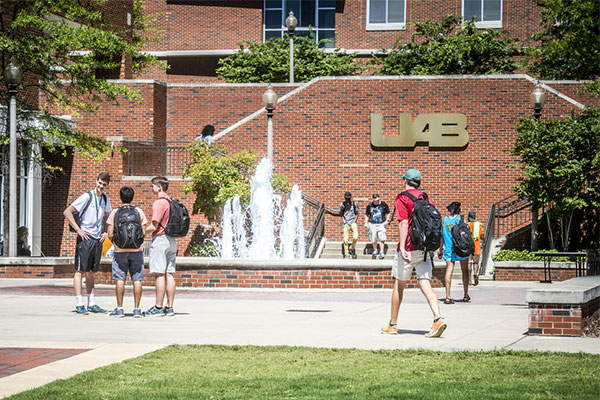 Students standing in front of building with UAB sign.