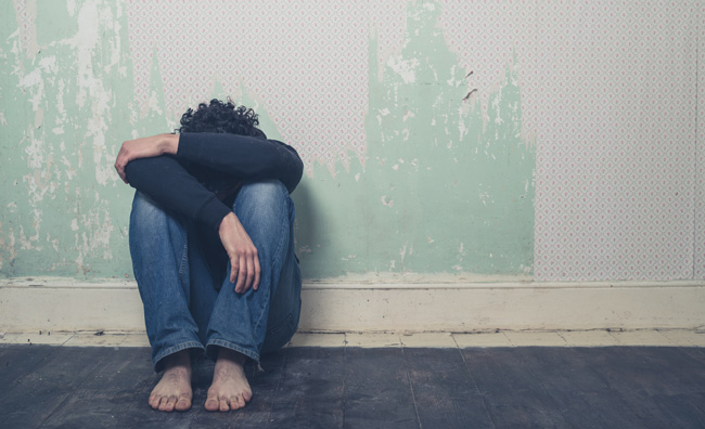 Barefooted depressed man with his head on his knees sitting against a wall.