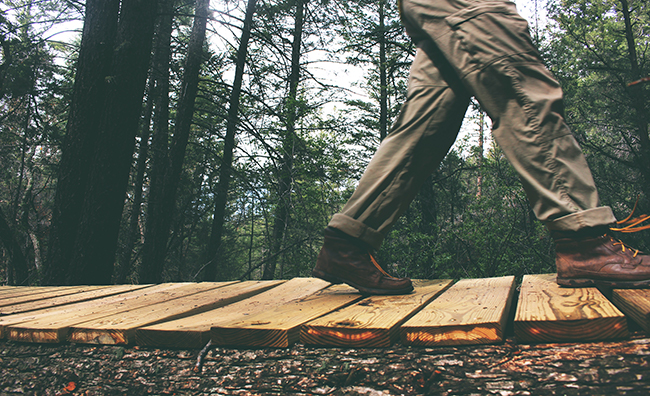 Legs of a person walking on a suspended wood bridge in the forest
