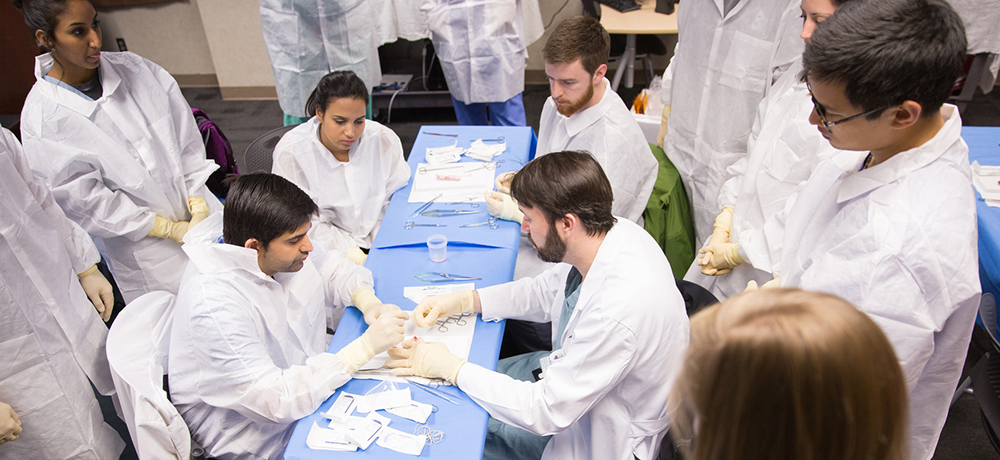 Division of Vascular Surgery and Endovascular Therapy Director Dr. Adam Beck teaches medical students about suturing at a vascular simulation activity.