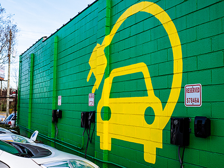 Large yellow electric vehicle painted on green background on concrete wall in front of the electric vehicle parking spaces, 2018.